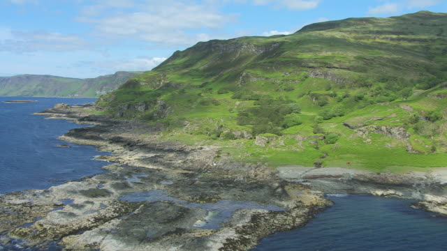 vídeos de stock e filmes b-roll de ms aerial ts shot low along cliffs on south coast near carsaig in hebrides on west coast to rocky shore / isle or island of mull, argyll and bute, scotland - ilha mull