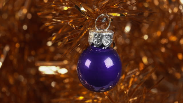 shot moving over a blue bauble decorating a gold tinsel christmas tree. - tinsel stock videos & royalty-free footage