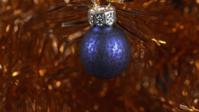 shot moving over a blue christmas bauble hanging from a gold tinsel tree. - tinsel stock videos & royalty-free footage