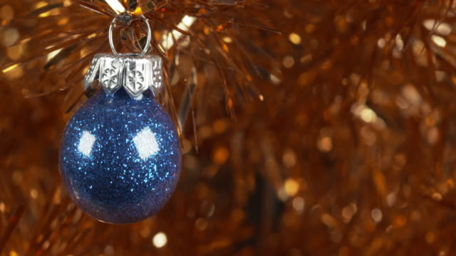 shot moving over a blue glitter bauble hanging from a gold christmas tree. - christmas decoration stock videos & royalty-free footage
