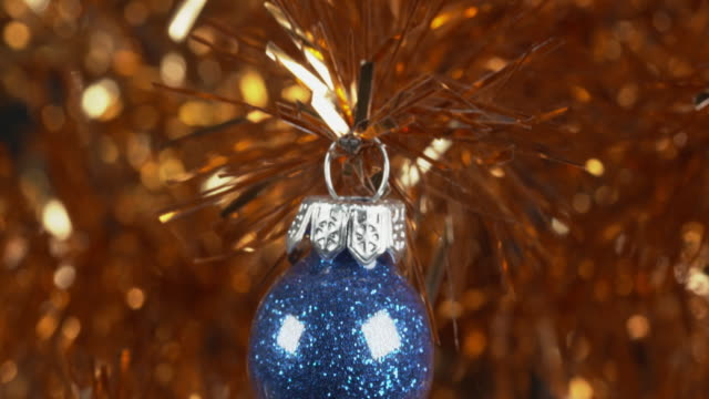 Shot moving over a blue glitter Christmas bauble hanging from a gold tinsel tree.