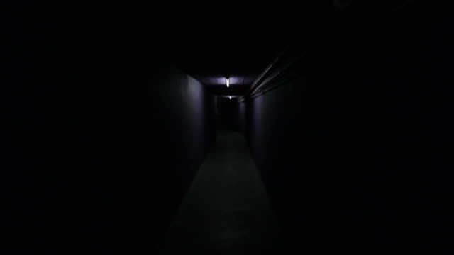 pov shot moving through dark corridor - telecamera traballante video stock e b–roll