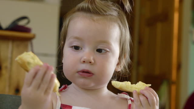 cu shot of 14 month-old toddler inspects and eating bagel / manistique, michigan, united states - bagel stock videos & royalty-free footage