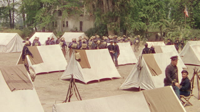 ms shot of 1840 us army camp, soldiers and tents with trees in background - neunzehntes jahrhundert stock-videos und b-roll-filmmaterial