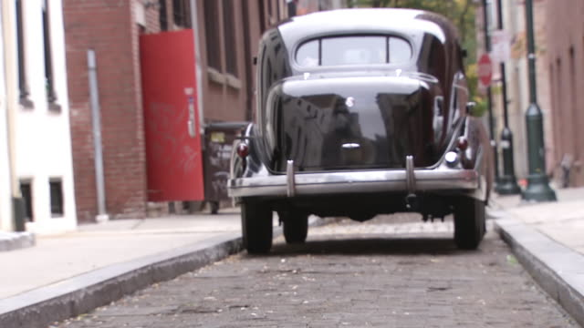 cu zi ts shot of 1930s lasalle car pulls off sidewalk and drives down street / philadelphia, pennsylvania, united states - 立ち去る点の映像素材/bロール