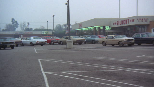 ms ts shot of 1970 blue ford mustang car on parking lot of shopping center  - 1970 stock-videos und b-roll-filmmaterial