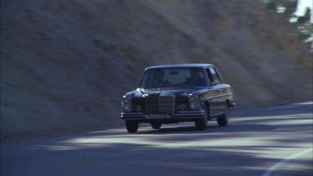 ms ts shot of 1972 black mercedes sedan drifting on mountain highway  - careless stock videos & royalty-free footage