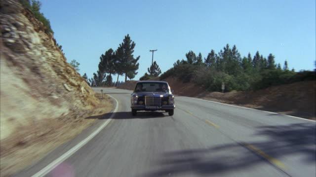 ms pov shot of 1972 black mercedes sedan on mountain highway - limousine luxuswagen stock-videos und b-roll-filmmaterial