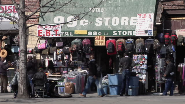 ms shot of 99 cents store in harlem with various suitcases and bags are seen hanging above shop entry / new york, united states - harlem stock videos & royalty-free footage
