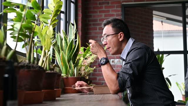 vídeos de stock, filmes e b-roll de foto de um empresário asiático comendo comer comida no escritório de vacas durante o intervalo do almoço - etnia oriental