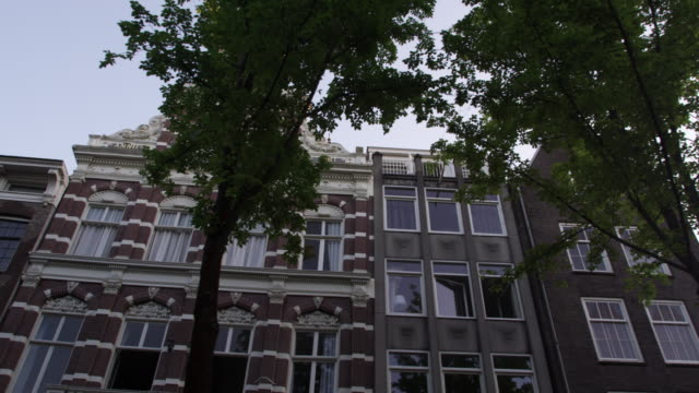 shot of a beautiful ancient building on a street in amsterdam - boat point of view stock videos and b-roll footage
