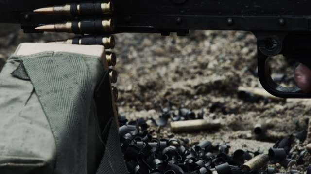 shot of a belt-fed machine gun as it is fired. - cartridge stock videos and b-roll footage