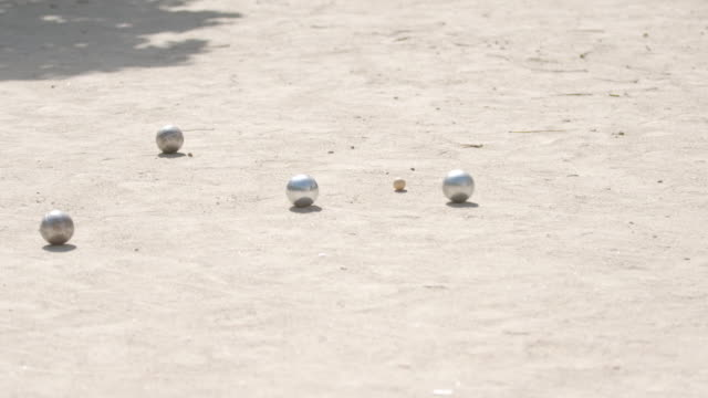 Shot of a boule rolling along the sand covered pavement towards stationary boules in the Place Dauphine, Paris.