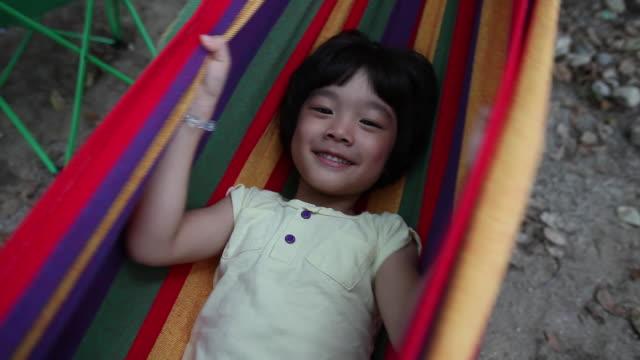 vídeos de stock, filmes e b-roll de shot of a boy playing in hammock - esconder
