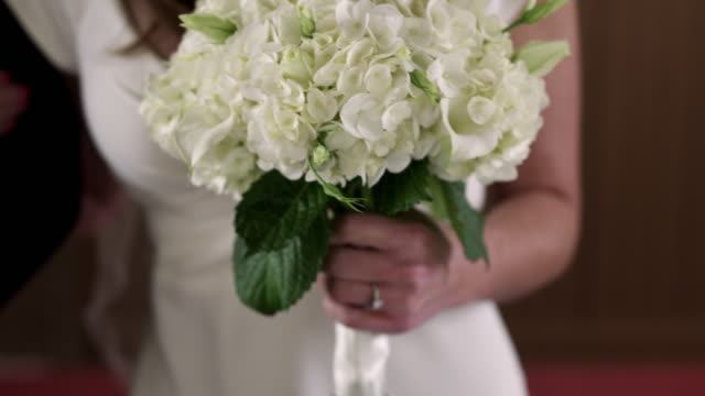 shot of a bride's wedding ring and bouquet as she walks down the aisle. - bride stock videos and b-roll footage