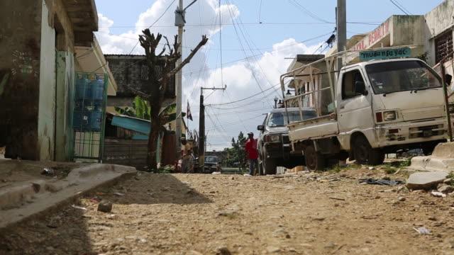 santa domingo dominican republic november 29 2012 shot of a broken road in the poor neighbourhood 'los alcarrizos' in santa domingo - insel hispaniola stock-videos und b-roll-filmmaterial