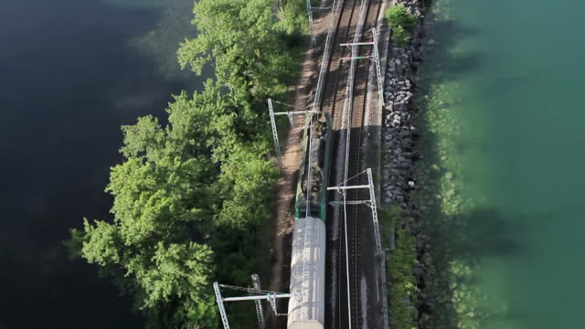 WS AERIAL SLO MO TS Shot of a cargo train traveling next to a lake in the french alps / chambery, savoir, france