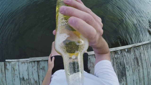 vídeos de stock e filmes b-roll de a pov shot of a caucasian man drinking a beer on the dock of a lake - 4k - beer alcohol
