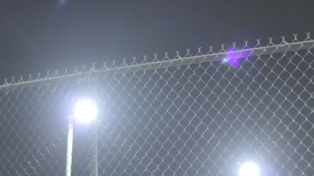 shot of a chain linked fence shot at night with light in background - chainlink fence stock videos and b-roll footage