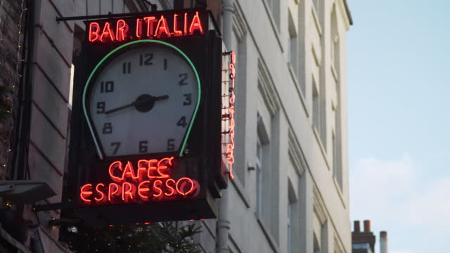 shot of a clock adorning the exterior of bar italia coffee bar in london's soho district. - schild stock-videos und b-roll-filmmaterial