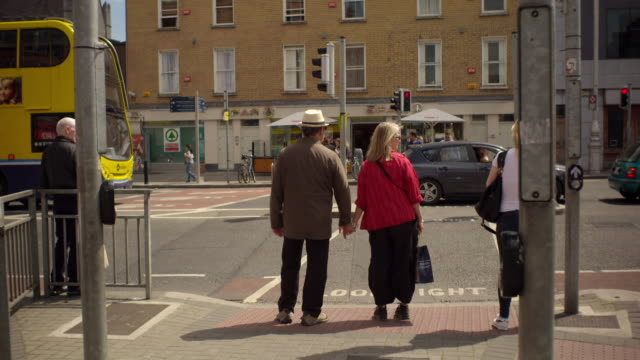 shot of a couple waiting to cross at an intersection in dublin, ireland on a summer day. traffic and bicycles pass by the road - abwarten stock-videos und b-roll-filmmaterial