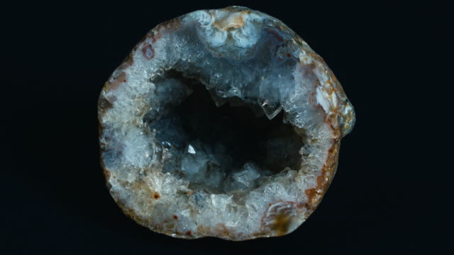 Shot of a cross section of a geode slowly revolving, displaying a beautiful crystal interior.