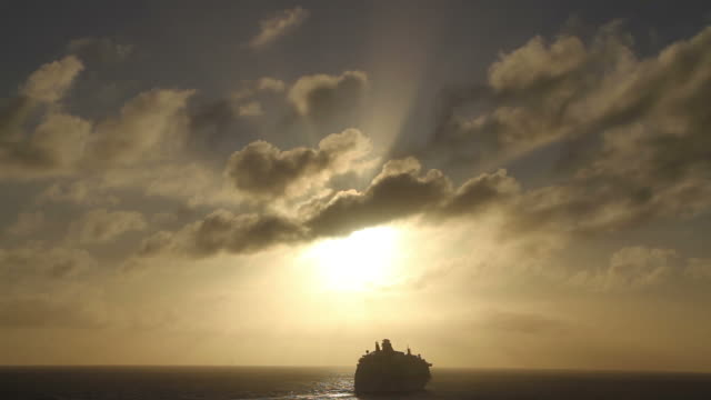 Shot of a cruise ship right under the sunset