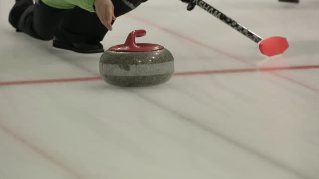 Shot of a curling stone moving on the ic