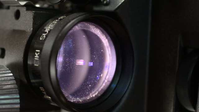 cu shot of a eike 16mm film projector lens.  the lens flickers while the footage goes through the frame.  - film stock videos & royalty-free footage