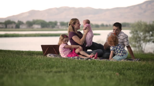 a shot of a family having a picnic by a lake on a slightly breezy day. - picnic stock-videos und b-roll-filmmaterial
