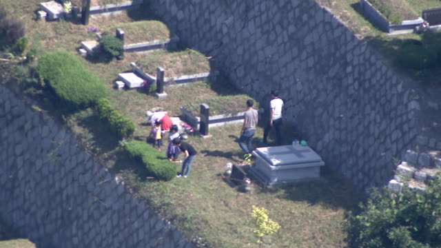 Shot of a family repairing grave at the cemetery park after performing ancestral rites