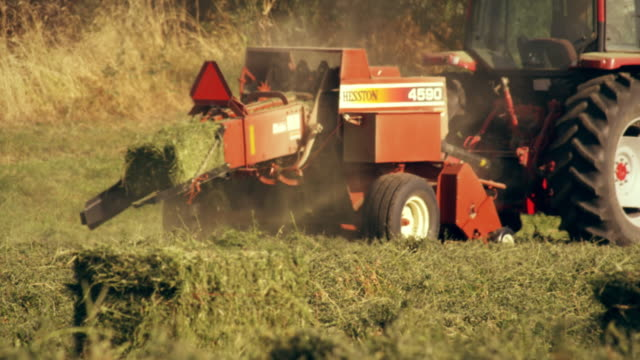 shot of a farmer operating a hay baler as he goes around the field - 干し草点の映像素材/bロール