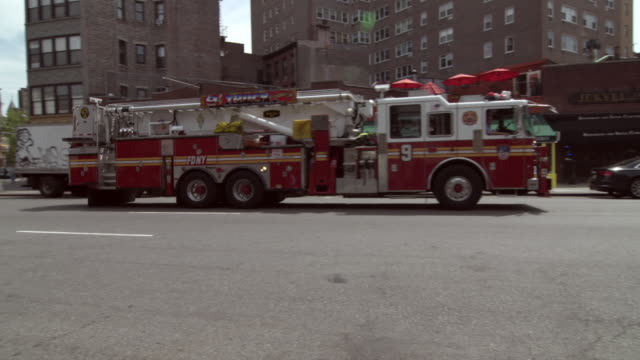 shot of a fdny truck turning onto a street in downtown manhattan - fire department of the city of new york stock-videos und b-roll-filmmaterial
