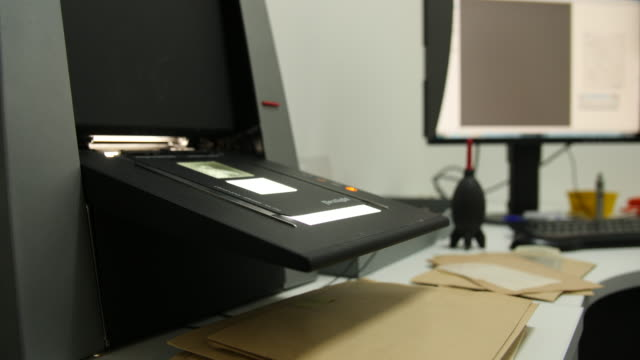 Shot of a film negative being fed into a digital negative scanner