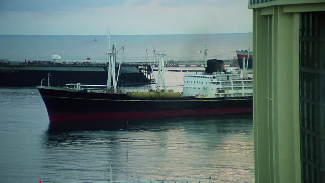 shot of a freighter arriving to an italian port in 1979 - cargo ship stock videos & royalty-free footage