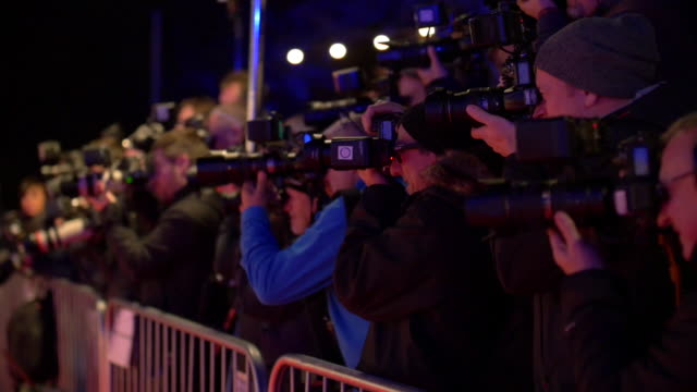 shot of a group of paparazzi photographers shooting celebrities at a red carpet premiere event - kamera blitzlicht stock-videos und b-roll-filmmaterial