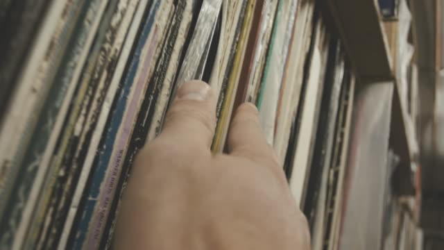POV shot of a hand gliding along a shelf of old vinyl records.
