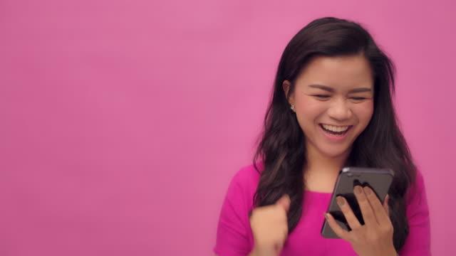 vídeos de stock, filmes e b-roll de slo mo disparado de uma mulher asiática feliz que usa o estúdio do smartphone disparado fundo cor-de-rosa gesto de mão feliz - fundo rosa