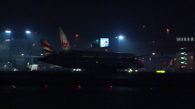 Shot of a Japanese Airlines aircraft reversing with it's tail fin illuminated on the tarmac at night at Heathrow Airport London