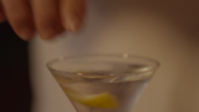 Shot of a lemon slice being squeezed and dropped into a cocktail glass filled with vermouth