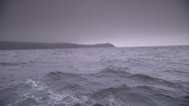 pov shot of a lighthouse on headland on county cork's coast, ireland, from choppy waters. - boat point of view stock videos & royalty-free footage
