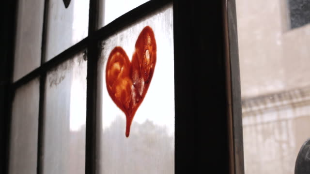 shot of a love heart painted onto a window pane. - partiell lichtdurchlässig stock-videos und b-roll-filmmaterial