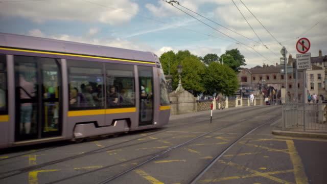vidéos et rushes de shot of a luas train going by in dublin, ireland on a summer day - ligne de tramway