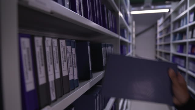 stockvideo's en b-roll-footage met shot of a male browsing and selecting digibeta tapes off shelving - bbc archives