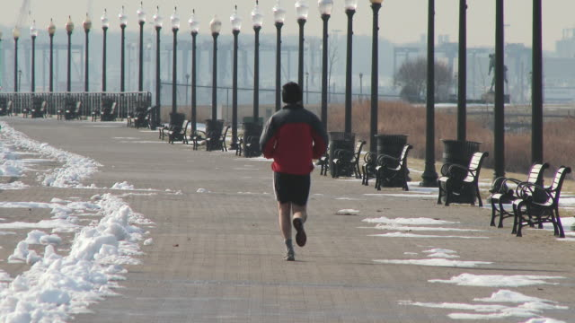 shot of a man jogging through liberty state park on a cold winter day. - shorts stock videos & royalty-free footage