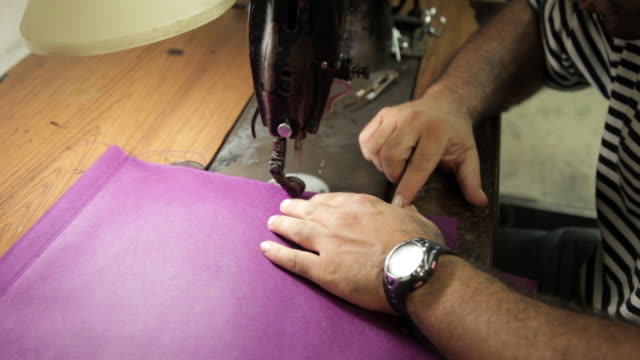 shot of a man sewing a seam onto a piece of pink fabric. - sewing stock videos & royalty-free footage
