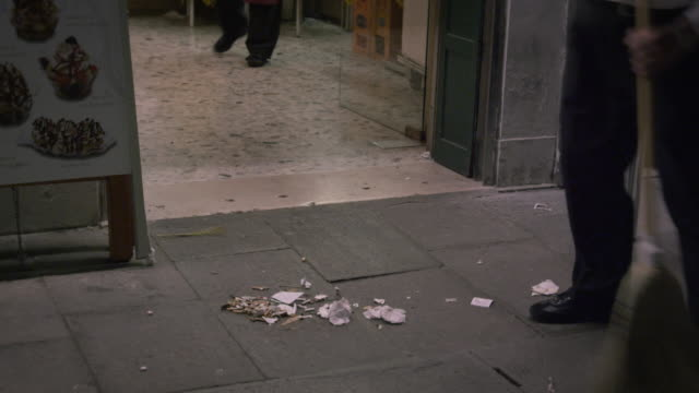 Shot of a man sweeping up the outdoor eating area in front of an Italian cafe.