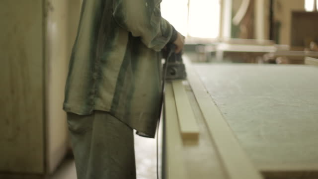 shot of a man using an electric sander on a length of wood. - 研磨器点の映像素材/bロール