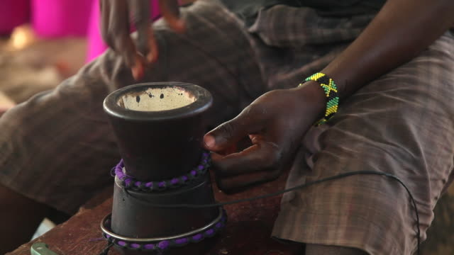 vidéos et rushes de shot of a man weaving threads around a small hand drum. - tisser