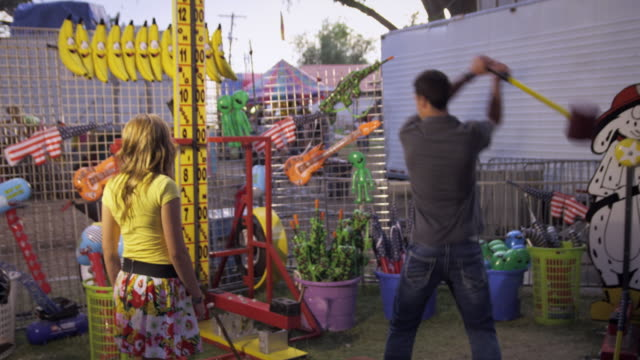 Shot of a man, with a girl, swinging a hammer at a carnival game.